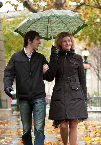 相合傘で腕を組む女性