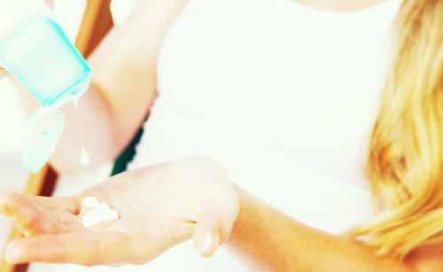 日焼け止めを手に塗る女性