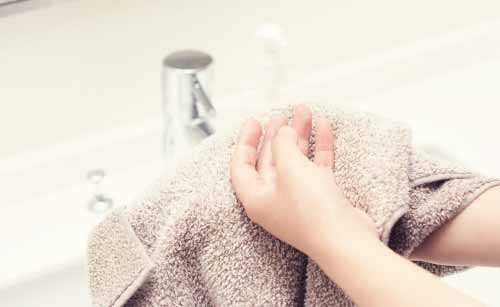 タオルで手を拭く女性