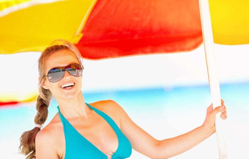 海で日傘をさす女