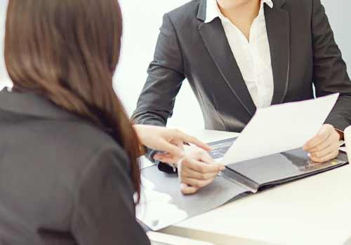 上司に書類の内容を話す女性