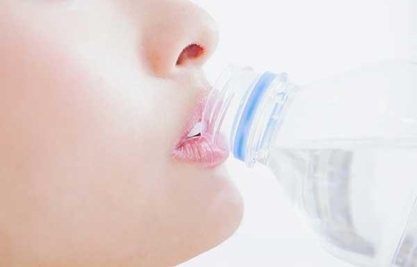 水を飲む若い女性