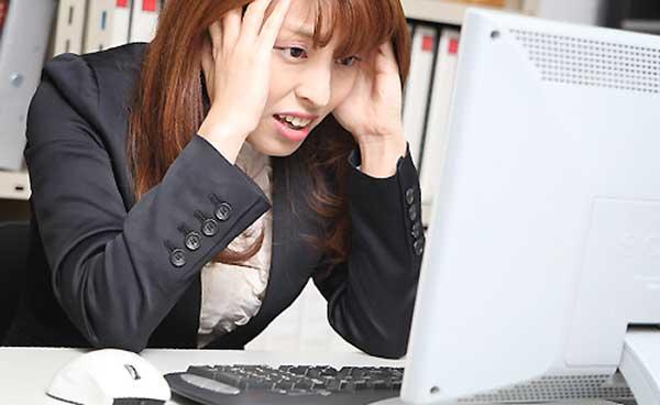 PCとにらめっこしている女性