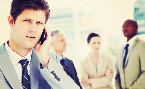 仕事場で電話を受け困る男性