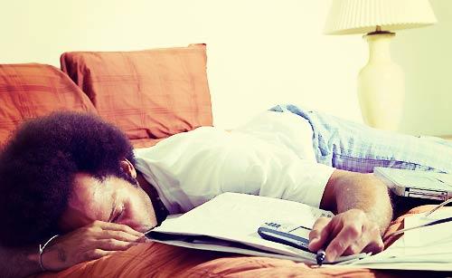 寝ている男性の前で鳴り続ける電話