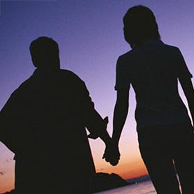 夕闇の中で手をつなぐ夫婦