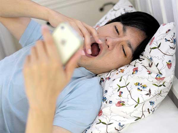 眠そうに携帯電話を見る男性