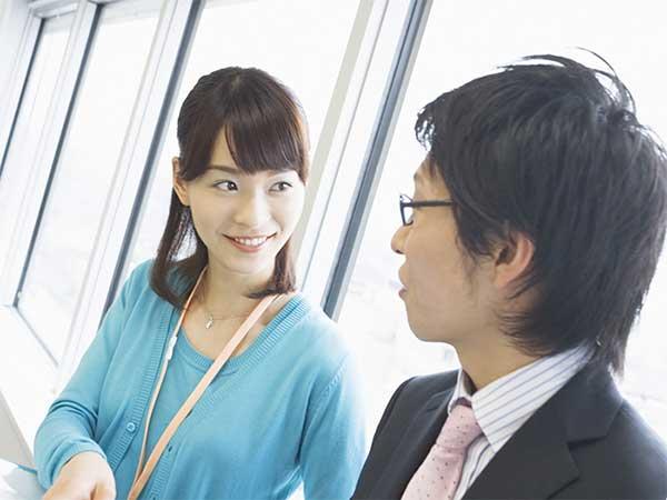 女性社員と話をするスーツ姿の男性