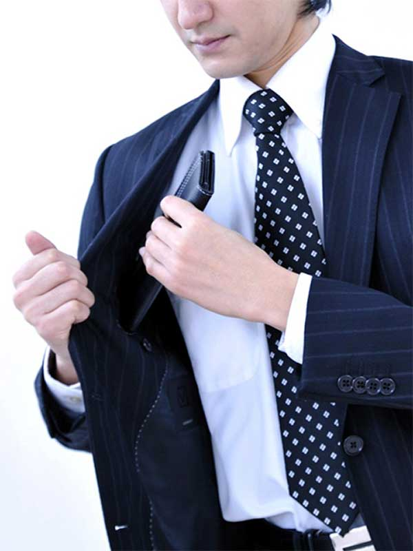 スーツの内ポケットから財布を取り出そうとしている男性