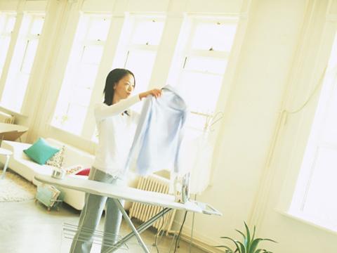 シャツにアイロンをかける女性