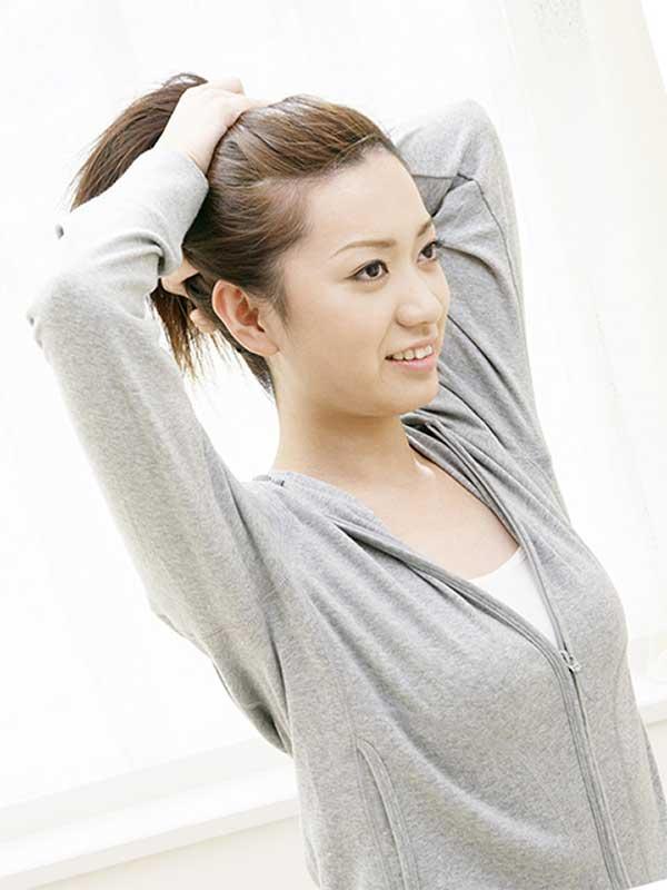 髪をアップにしようとしている女性