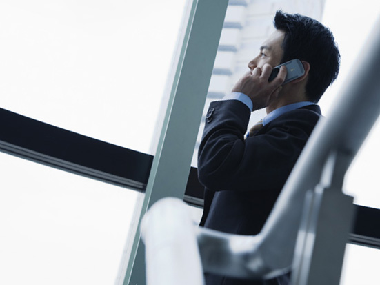 非常階段でこっそりと電話するスーツ姿の男性