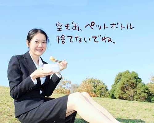 公園の芝に座って弁当を食べている女性