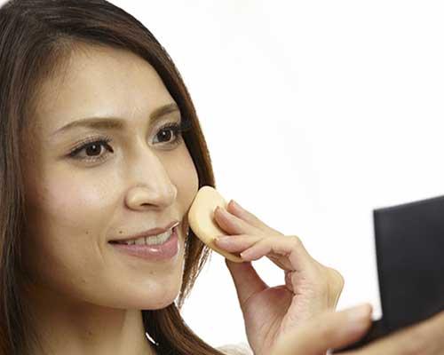 携帯ファンデーションで、お化粧する女性