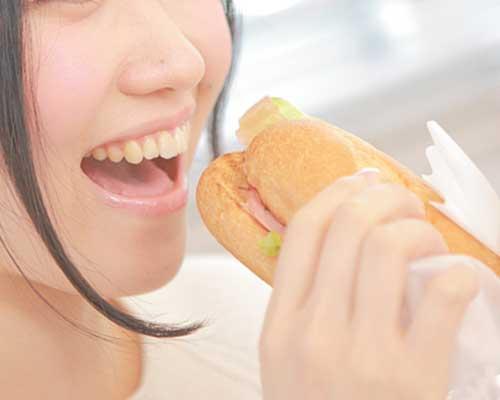 サンドイッチを頬張る女性