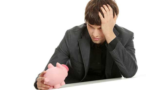 豚の貯金箱を見て落ち込む男性
