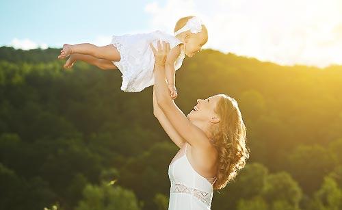 赤ん坊を抱え上げる母親