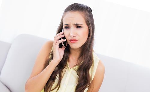 複雑な心境で電話をする女性