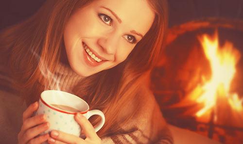 飲み物で体を温める女性