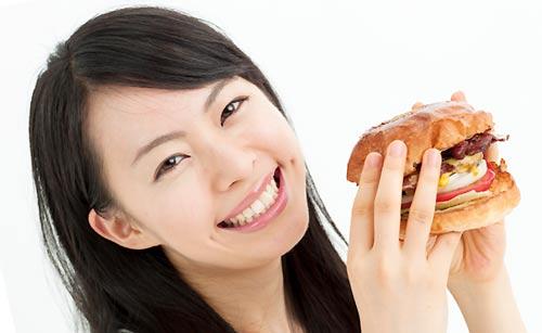 美味しそうにハンバーガーを食べる女性