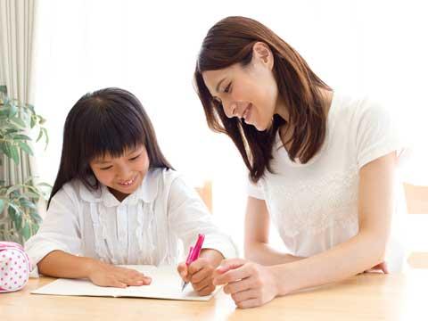 子供の勉強を見てあげてる女性