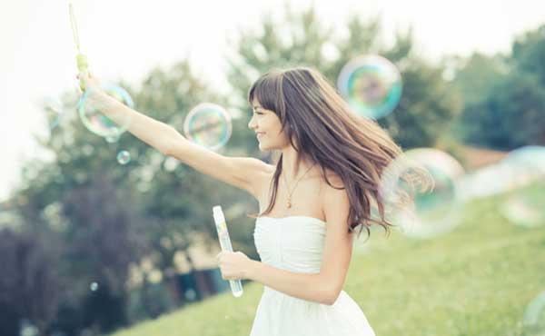 子どもっぽくシャボン玉で遊ぶ女性