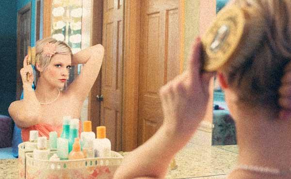自分を変えようと鏡の前に立つ女性