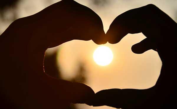 愛の光を作るハートの手
