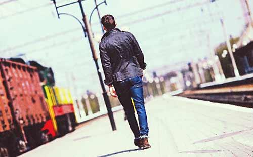 駅のホームを歩く男