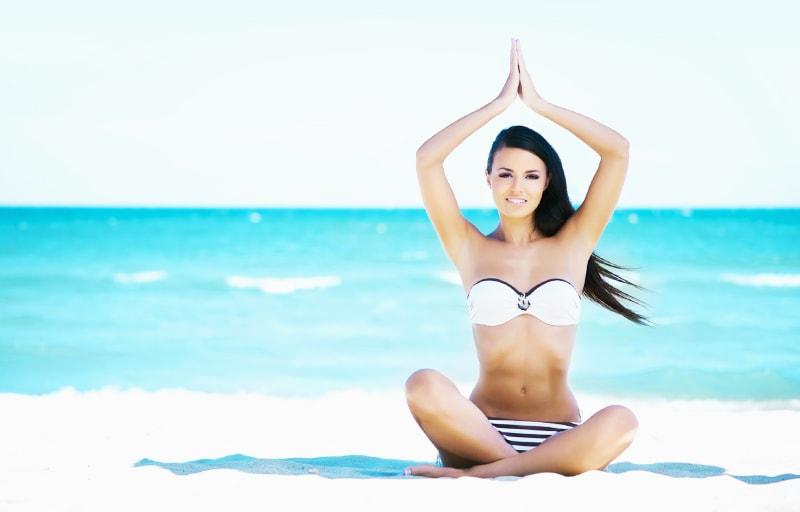 砂浜でヨガをしている女