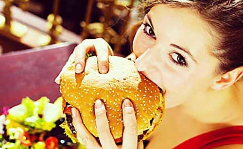 大きいハンバーガーを食べる女性