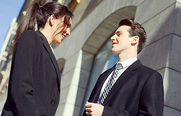 会話するスーツ姿の男女