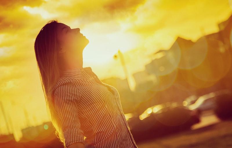 夕日を見上げる女