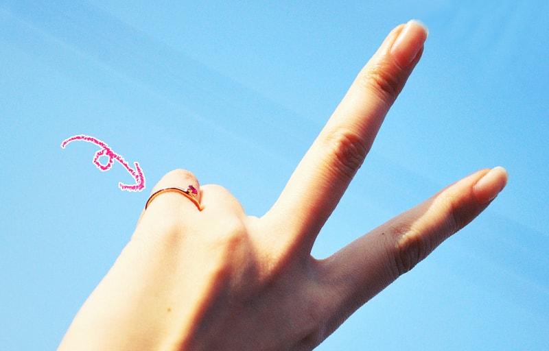 ピンクーリングをはめたVサイン