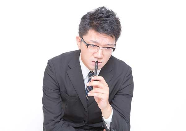 鉛筆の端を噛む男性