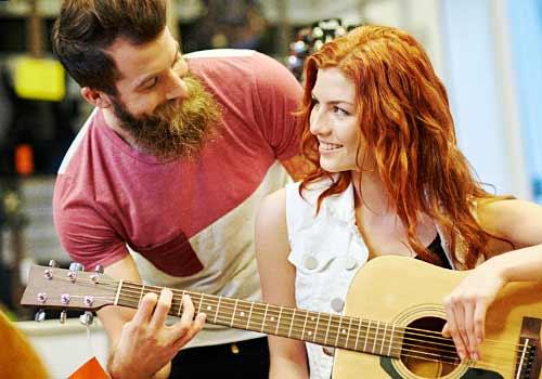 一緒にギターを弾くカップル
