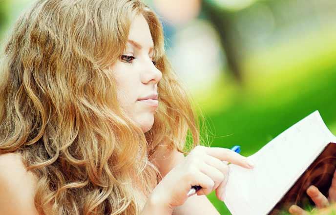 手帳にスケジュールを書く女性