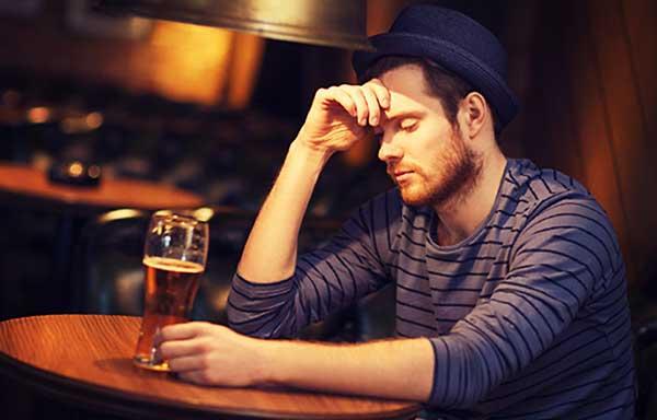 一人酒場で悩む男