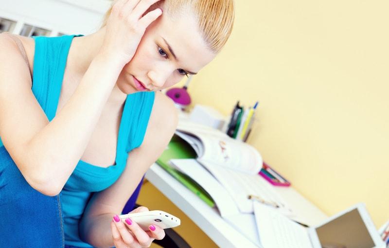 電話をかけるか悩んでいる女子