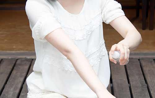 虫除けスプレーをかける女性