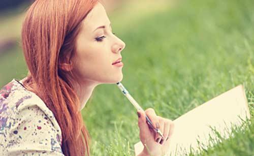 紙に何かを書く女性