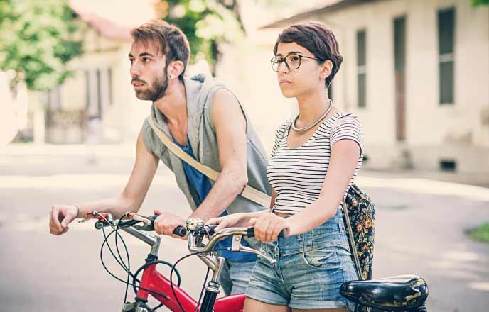 自転車で街を移動するカップル