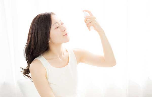 化粧水を顔にかける女性