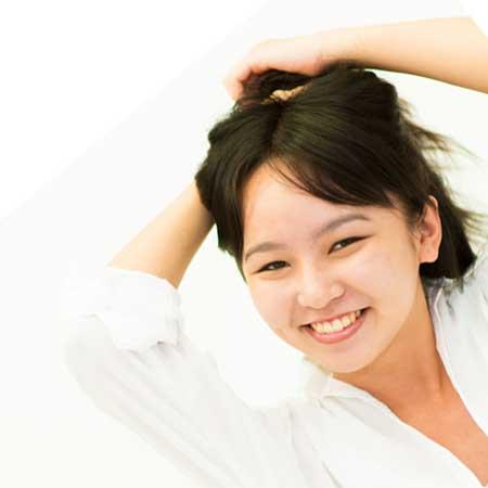 髪を掻き揚げる女性