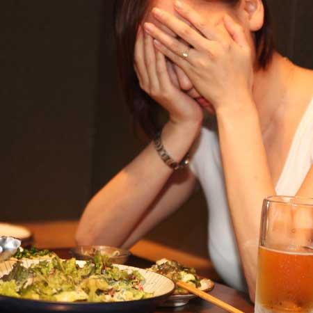 居酒屋で顔を両手で隠す女性