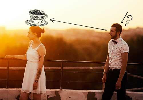頭にコーヒーカップを乗せた女性に気づく男性