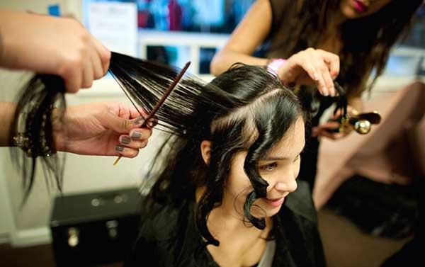 美容師に髪を手入れしてもらう女