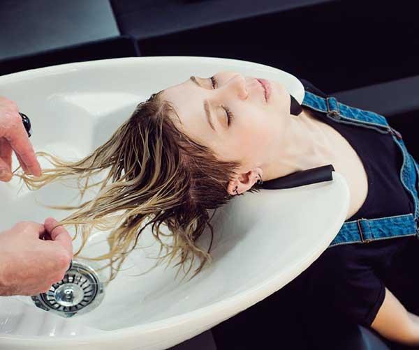 美容師にシャンプーしてもらう女