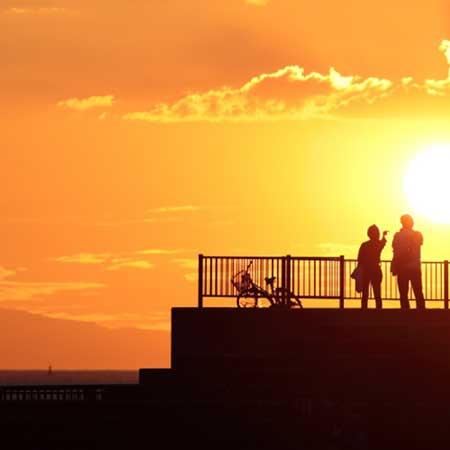 夕日景勝地に立つカップル