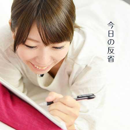 ノートに日記を書く女性